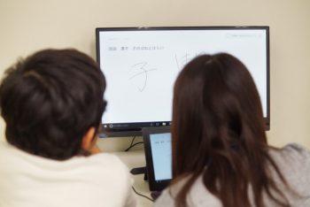 学習支援でモニターを使って漢字の書き方を確認する一コマ
